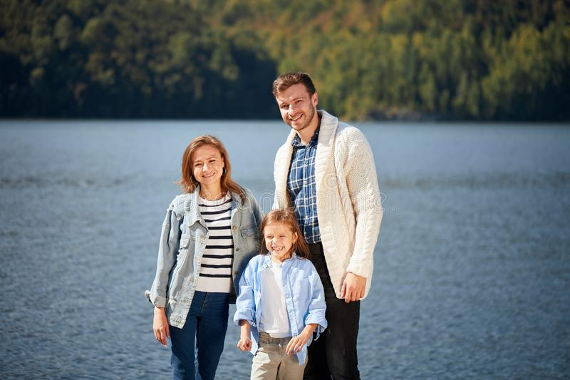 Ευτυχής οικογένεια που εξετάζει τη κάμερα θέτοντας στην αποβάθρα στην ήρεμη λίμνη στοκ φωτογραφίες με δικαίωμα ελεύθερης χρήσης