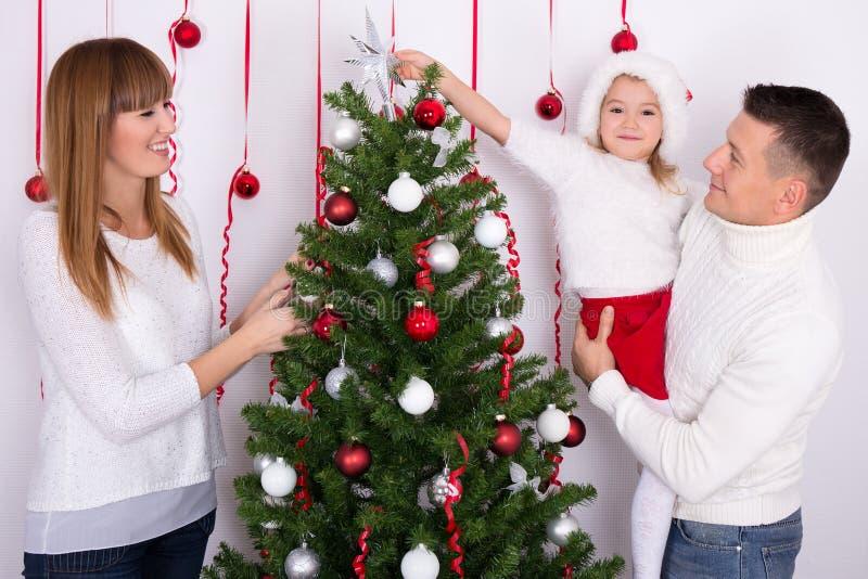 Ευτυχής οικογένεια που διακοσμεί το χριστουγεννιάτικο δέντρο στο σπίτι στοκ εικόνα