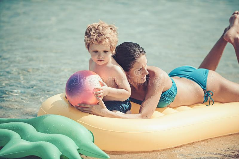 Ευτυχής οικογένεια που κολυμπά σε ένα στρώμα αέρα, μητέρα και chil από κοινού στοκ φωτογραφία