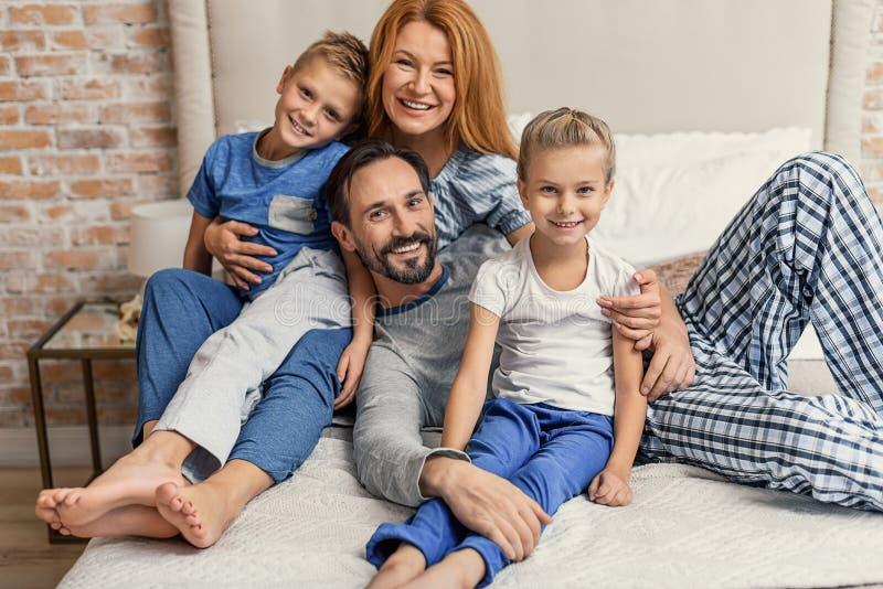 Ευτυχής οικογένεια που ξαπλώνει στο κρεβάτι στο σπίτι στοκ εικόνες