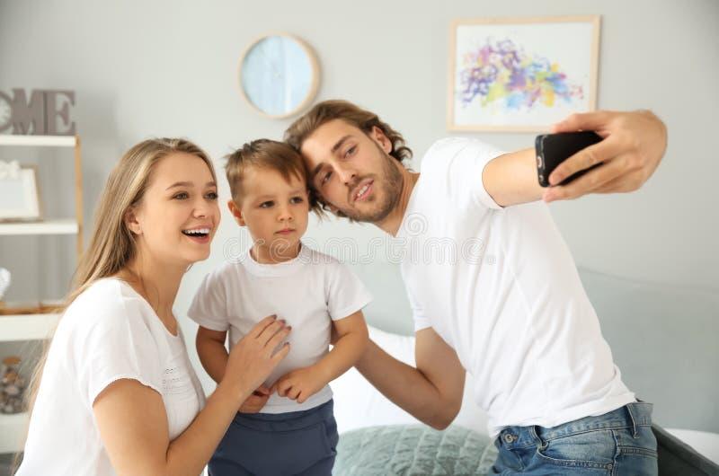Ευτυχής οικογένεια που παίρνει selfie στην κρεβατοκάμαρα στοκ εικόνα