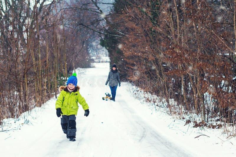 Ευτυχής οικογένεια που περπατά καιρό χειμερινού στο δασικό χειμώνα Ευτυχής μητέρα και ο γιος της που απολαμβάνουν τη χιονώδη χειμ στοκ φωτογραφία