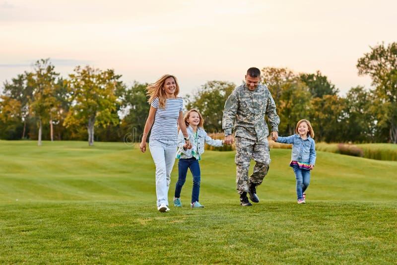 Ευτυχής οικογένεια που περπατά στη χλόη στοκ φωτογραφία με δικαίωμα ελεύθερης χρήσης
