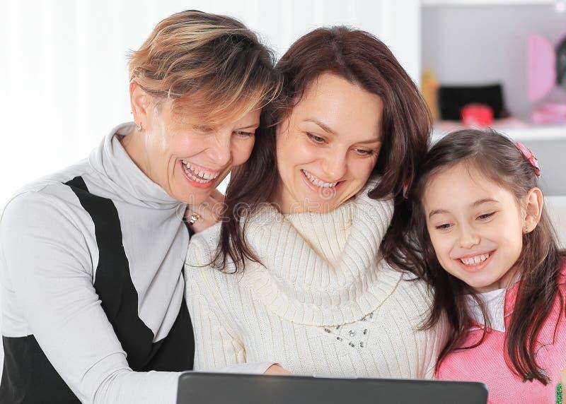 Ευτυχής οικογένεια που προσέχει μια αγαπημένη επίδειξη στο lap-top στοκ εικόνα με δικαίωμα ελεύθερης χρήσης