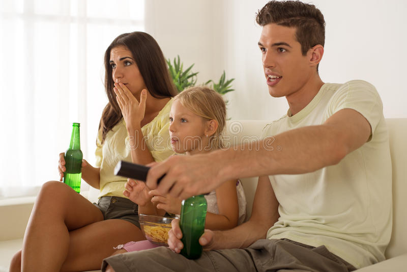 Ευτυχής οικογένεια που προσέχει στο σπίτι τη TV στοκ φωτογραφία