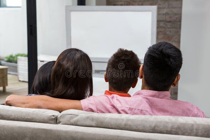 Ευτυχής οικογένεια που προσέχει τη TV στον καναπέ στοκ εικόνες με δικαίωμα ελεύθερης χρήσης
