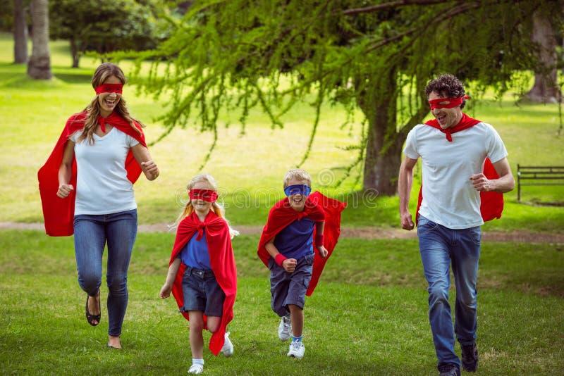 Ευτυχής οικογένεια που προσποιείται να είναι τρέξιμο superhero στοκ φωτογραφία με δικαίωμα ελεύθερης χρήσης