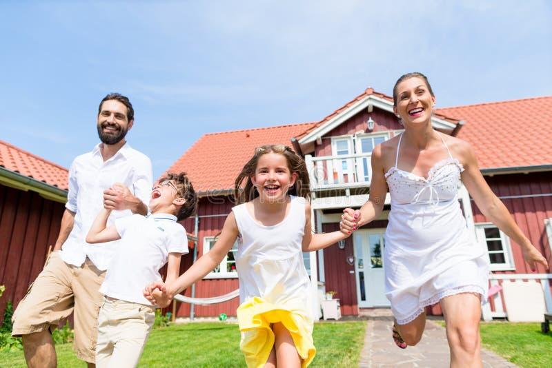 Ευτυχής οικογένεια που τρέχει στο λιβάδι μπροστά από το σπίτι στοκ εικόνες