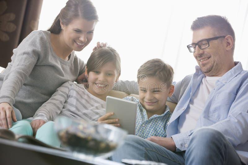 Ευτυχής οικογένεια που χρησιμοποιεί την ψηφιακή ταμπλέτα μαζί στο καθιστικό στοκ εικόνες