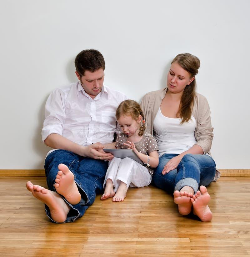 Ευτυχής οικογένεια που χρησιμοποιεί τον υπολογιστή ταμπλετών στοκ φωτογραφία