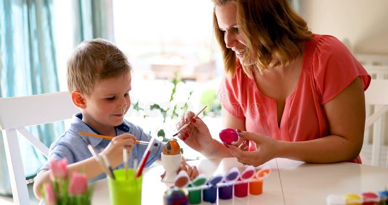Ευτυχής οικογένεια που χρωματίζει τα αυγά Πάσχας στοκ φωτογραφίες
