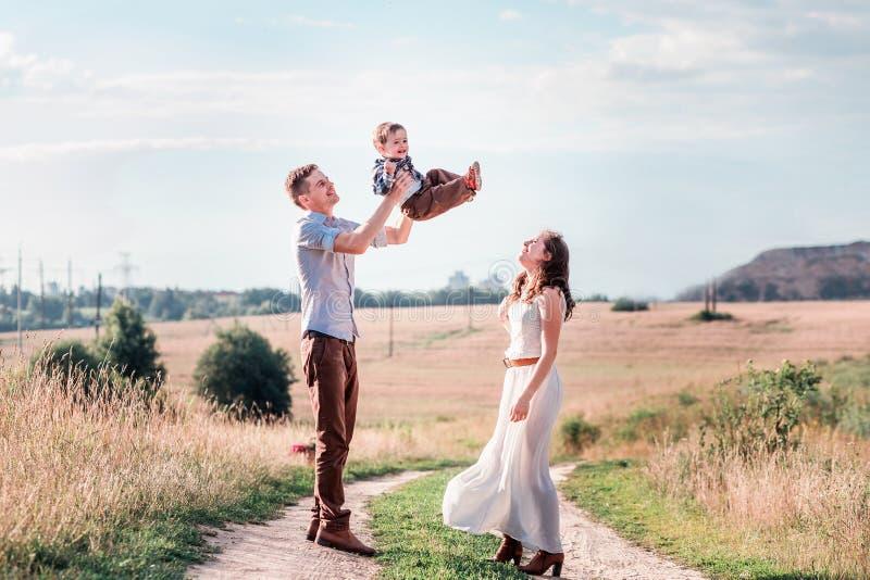 Ευτυχής οικογένεια σε έναν περίπατο στον τομέα Εκτίναξη πατέρων επάνω ο γιος του στοκ φωτογραφίες με δικαίωμα ελεύθερης χρήσης