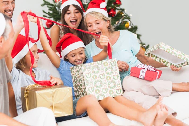 Ευτυχής οικογένεια στα δώρα ανοίγματος Χριστουγέννων από κοινού στοκ εικόνες