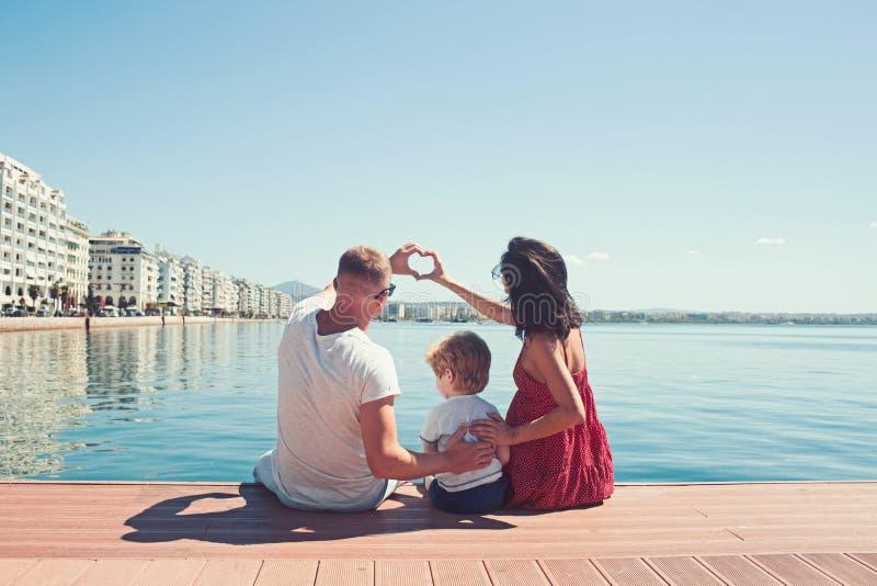 Ευτυχής οικογένεια στην παραλία Άνθρωποι που έχουν τη διασκέδαση στις θερινές διακοπές Μητέρα και παιδί πατέρων ενάντια στην μπλε στοκ εικόνες
