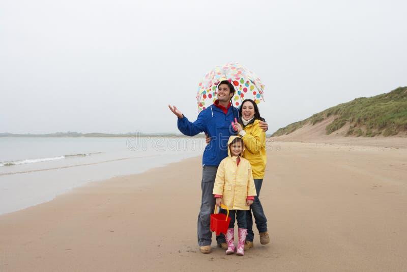 Ευτυχής οικογένεια στην παραλία με την ομπρέλα στοκ φωτογραφίες με δικαίωμα ελεύθερης χρήσης