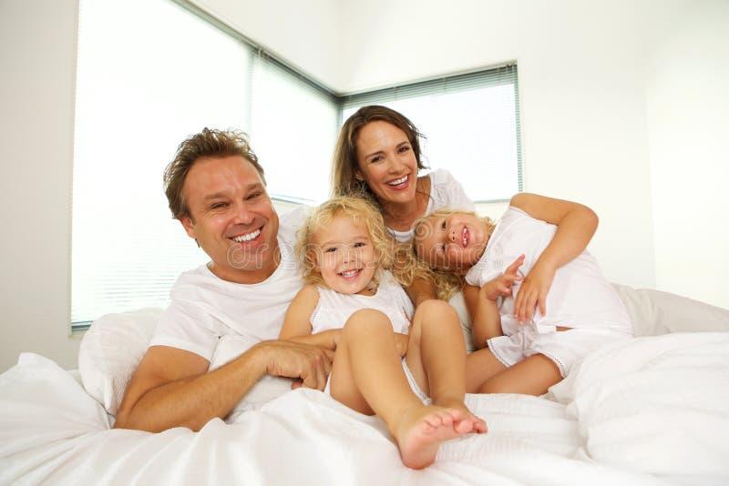 Ευτυχής οικογένεια στο κρεβάτι στην κρεβατοκάμαρα στοκ εικόνες