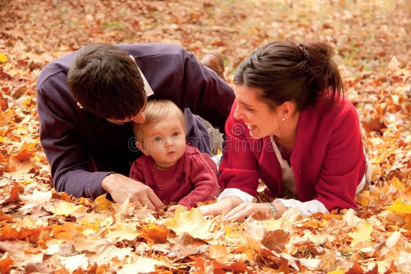 Ευτυχής οικογένεια στο πάρκο το φθινόπωρο στοκ εικόνα