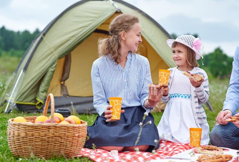 Ευτυχής οικογένεια στο πικ-νίκ στη στρατοπέδευση Μητέρα και κόρη που τρώνε κοντά σε μια σκηνή στο λιβάδι ή το πάρκο στοκ φωτογραφία με δικαίωμα ελεύθερης χρήσης