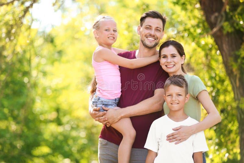 Ευτυχής οικογένεια στο πράσινο πάρκο τη θερινή ημέρα στοκ εικόνες