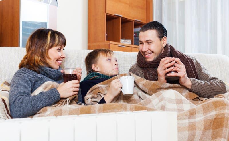 Ευτυχής οικογένεια τριών   θέρμανση κοντά στο θερμό θερμαντικό σώμα στοκ εικόνα με δικαίωμα ελεύθερης χρήσης