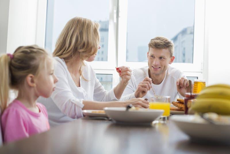 Ευτυχής οικογένεια τριών που έχουν το πρόγευμα στον πίνακα στοκ φωτογραφίες με δικαίωμα ελεύθερης χρήσης