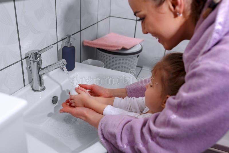 Ευτυχής οικογένεια - χέρια πλύσης παιδιών και μητέρων με το σαπούνι στο bathr στοκ φωτογραφίες