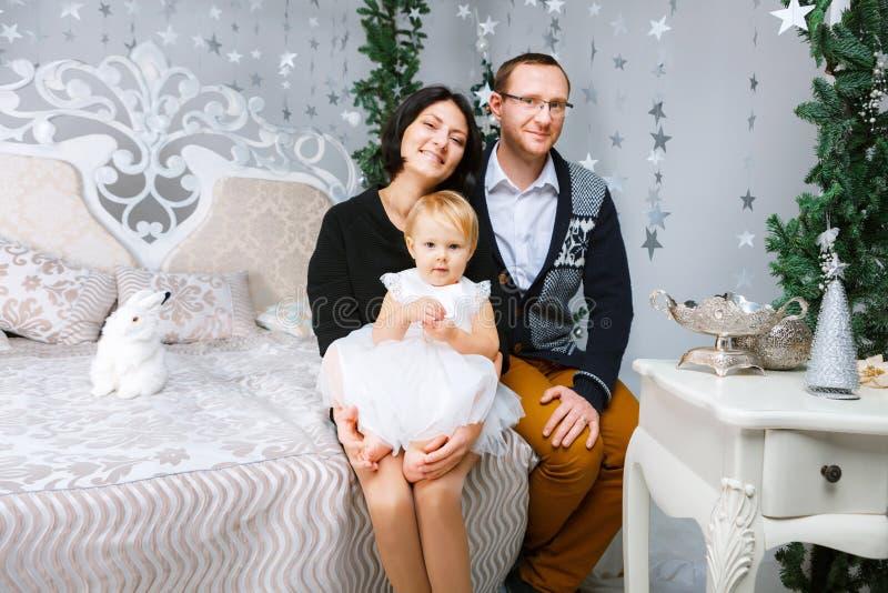 Ευτυχής οικογένεια Χριστουγέννων τριών ατόμων που κάθονται στο κρεβάτι του άσπρου υποβάθρου κρεβατοκάμαρων στοκ εικόνα με δικαίωμα ελεύθερης χρήσης