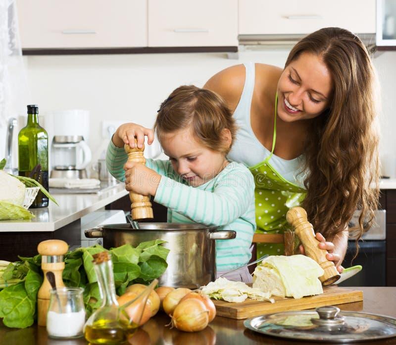 Ευτυχής οικογενειακή μαγειρεύοντας σούπα στοκ εικόνες