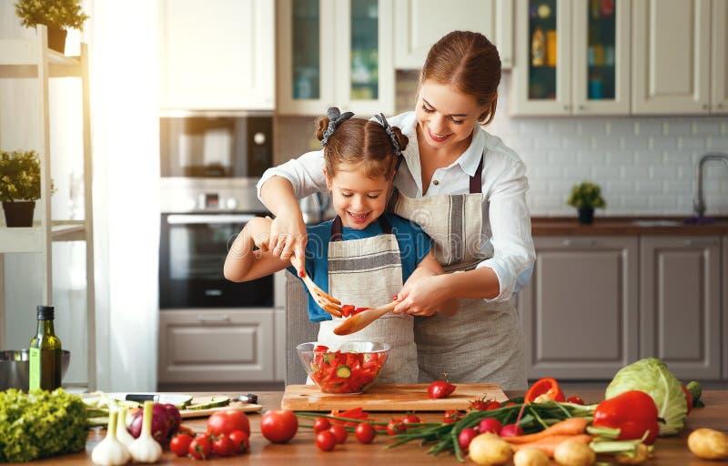 Ευτυχής οικογενειακή μητέρα με το κορίτσι παιδιών που προετοιμάζει τη φυτική σαλάτα στοκ φωτογραφία