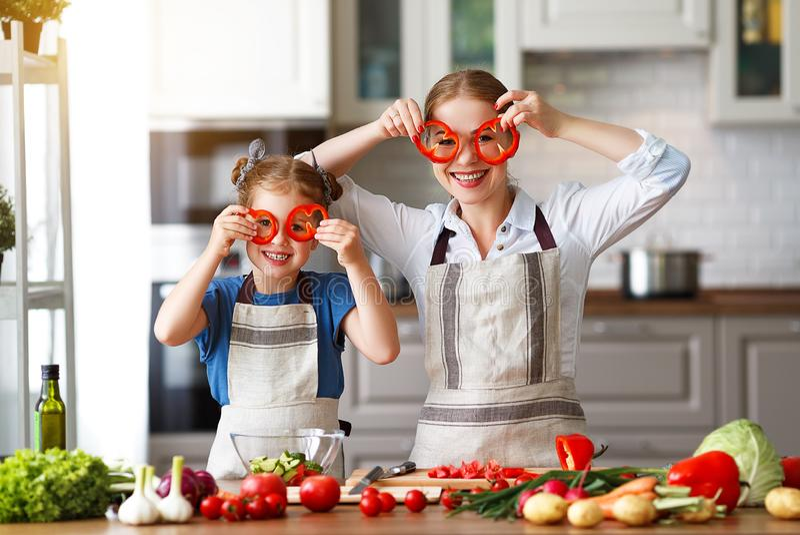 Ευτυχής οικογενειακή μητέρα με το κορίτσι παιδιών που προετοιμάζει τη φυτική σαλάτα στοκ φωτογραφίες