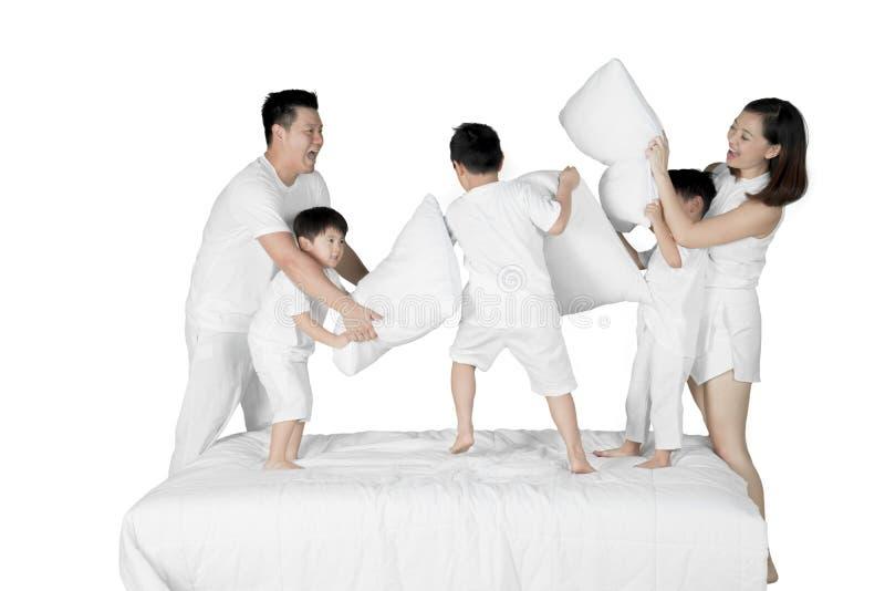 Ευτυχής οικογενειακή πάλη με τα μαξιλάρια στο στούντιο στοκ φωτογραφίες