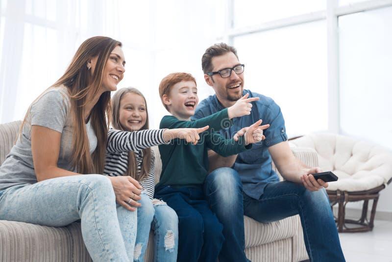 Ευτυχής οικογενειακή συνεδρίαση που προσέχει τη TV στο σπίτι τους στοκ εικόνες με δικαίωμα ελεύθερης χρήσης