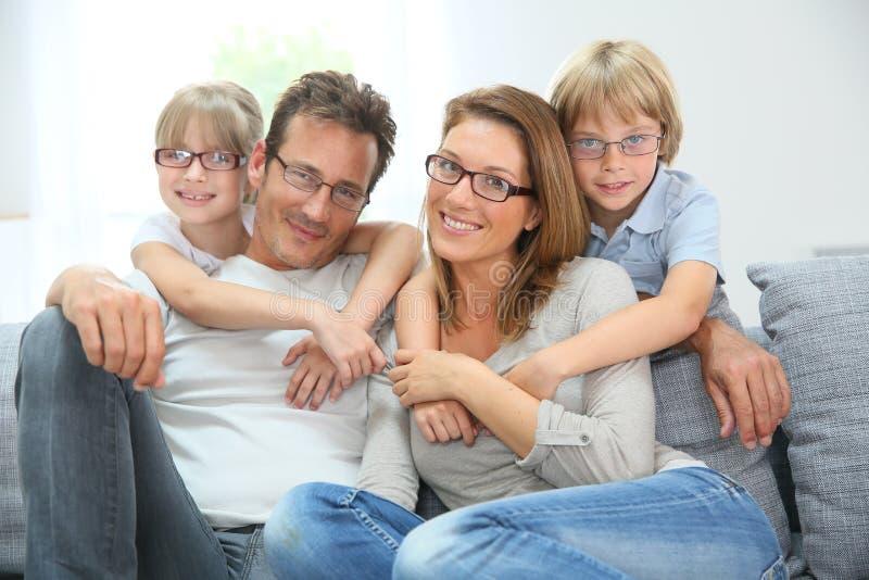 Ευτυχής οικογενειακή συνεδρίαση στον καναπέ που φορά eyeglasses στοκ φωτογραφίες