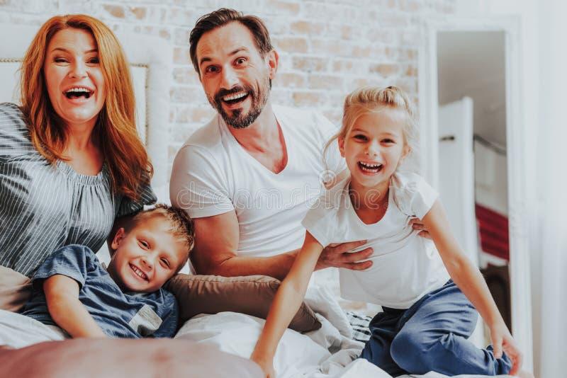 Ευτυχής οικογενειακή τοποθέτηση γέλιου στη κάμερα στο κρεβάτι στοκ φωτογραφία