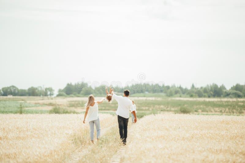 Ευτυχής οικογενειακός περίπατος στον τομέα σίτου την ηλιόλουστη ημέρα στοκ εικόνες