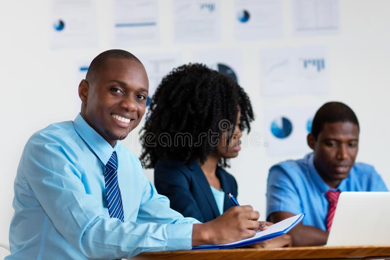 Ευτυχής οικονομικός σύμβουλος αφροαμερικάνων με την επιχειρησιακή ομάδα στοκ φωτογραφία
