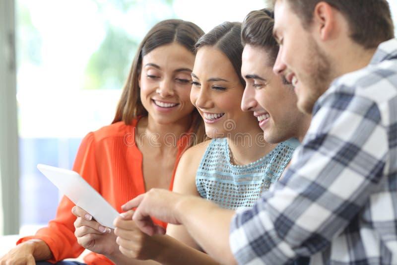 Ευτυχής ομάδα φίλων που ελέγχουν την ταμπλέτα στο σπίτι στοκ φωτογραφία