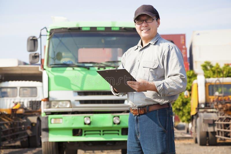 Ευτυχής οδηγός φορτηγού που γράφει στο έγγραφο στοκ εικόνες