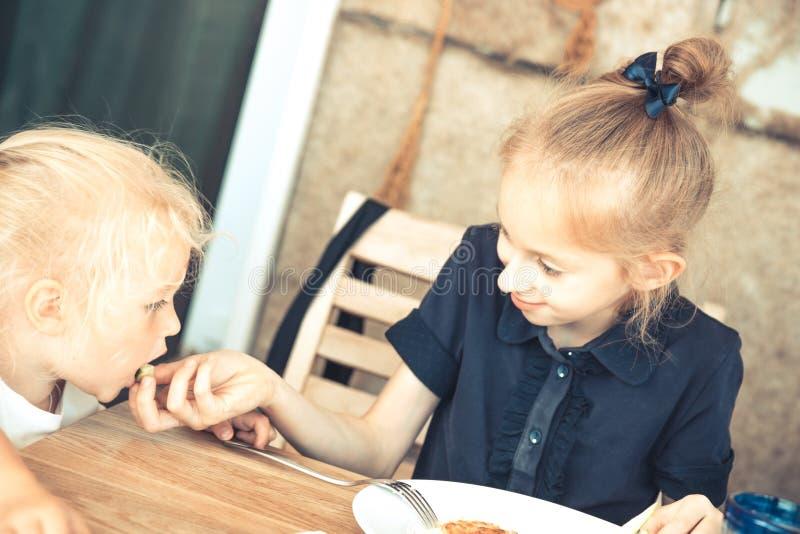 Ευτυχής παλαιότερη αδελφή που ταΐζει στη μικρή αδελφή στην έννοια εστιατορίων καφέδων τον τρόπο ζωής παιδικής ηλικίας παιδικής μέ στοκ εικόνα