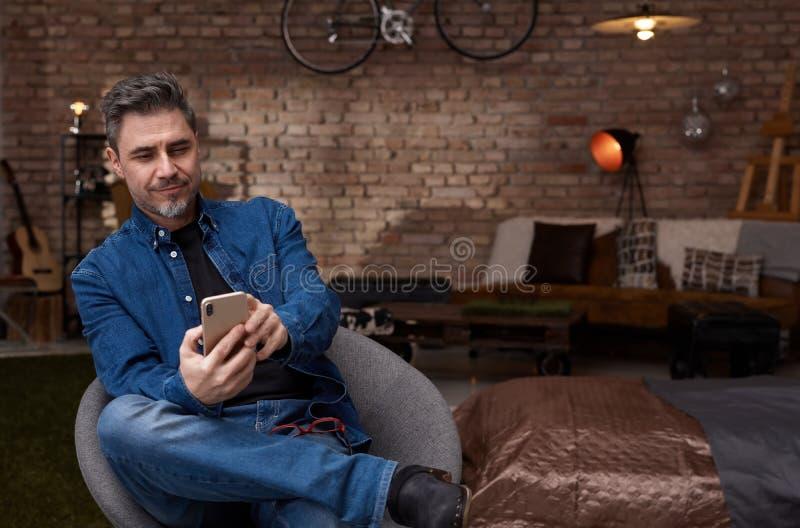 Ευτυχής παλαιότερος λευκός στο τηλέφωνο στο σπίτι στοκ φωτογραφία με δικαίωμα ελεύθερης χρήσης