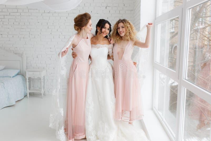Ευτυχής παράνυμφος που αγκαλιάζει τη νύφη στην κρεβατοκάμαρα το πρωί στοκ εικόνες με δικαίωμα ελεύθερης χρήσης