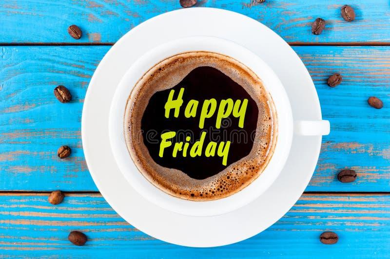 Ευτυχής Παρασκευή στο τοπ φλυτζάνι καφέ άποψης στο μπλε ξύλινο υπόβαθρο στοκ φωτογραφία με δικαίωμα ελεύθερης χρήσης