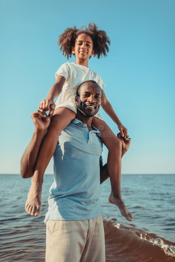 ευτυχής πατέρας αφροαμερικάνων που φέρνει λίγη κόρη στο λαιμό και που χαμογελά στη κάμερα στοκ φωτογραφίες