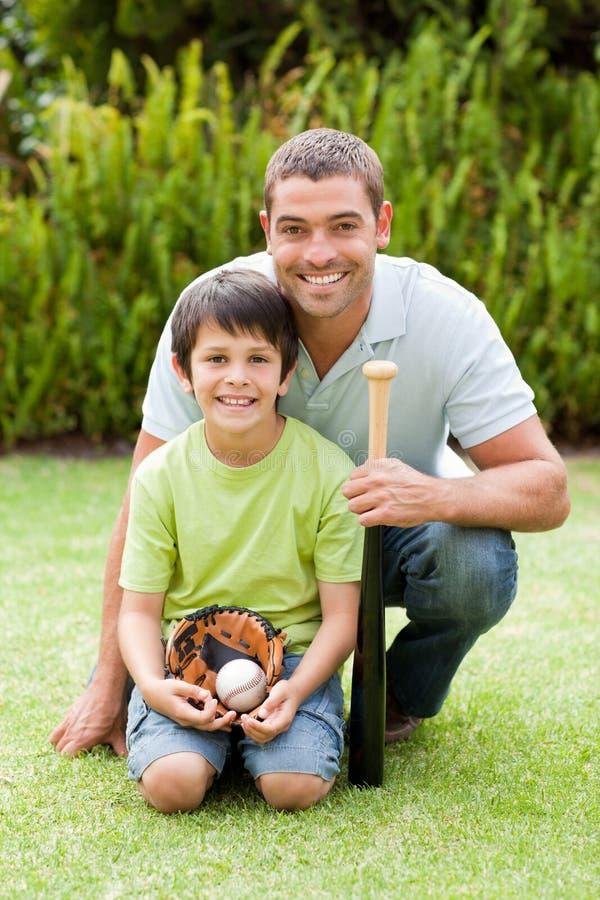 Ευτυχής πατέρας και το παίζοντας μπέιζ-μπώλ γιων του στοκ εικόνα με δικαίωμα ελεύθερης χρήσης