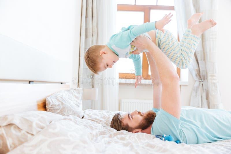 Ευτυχής πατέρας που βρίσκεται σε κακό και που παίζει με το γιο του στοκ εικόνα με δικαίωμα ελεύθερης χρήσης