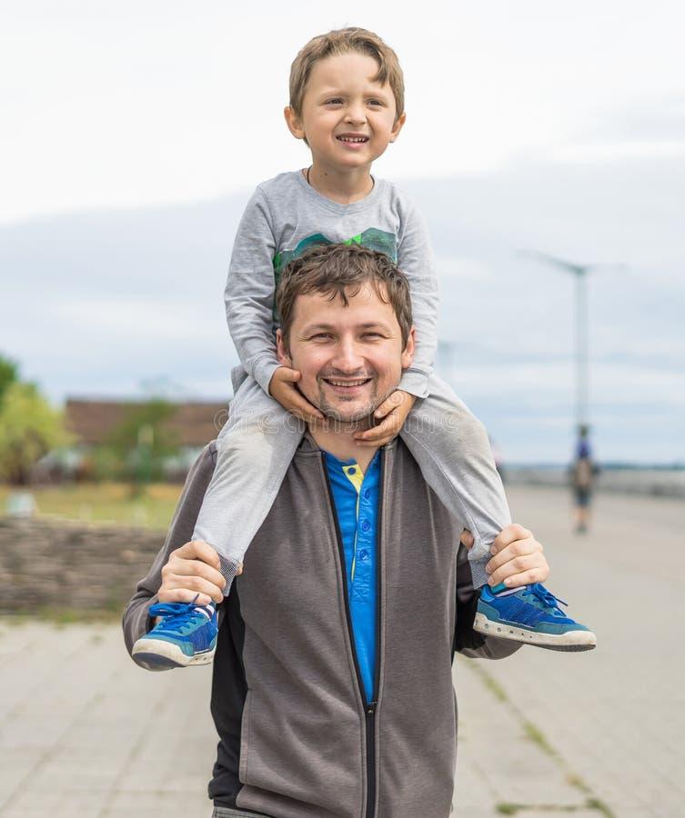 Ευτυχής πατέρας που δίνει το γύρο ώμων στους ώμους του στον κήπο Ευτυχές χαμογελώντας αγόρι στον μπαμπά ώμων που εξετάζει τη κάμε στοκ φωτογραφία με δικαίωμα ελεύθερης χρήσης