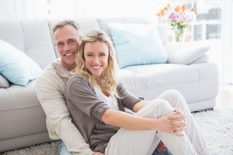 Ευτυχής περιστασιακή συνεδρίαση ζευγών στην κουβέρτα που χαμογελά στη κάμερα στοκ φωτογραφία με δικαίωμα ελεύθερης χρήσης