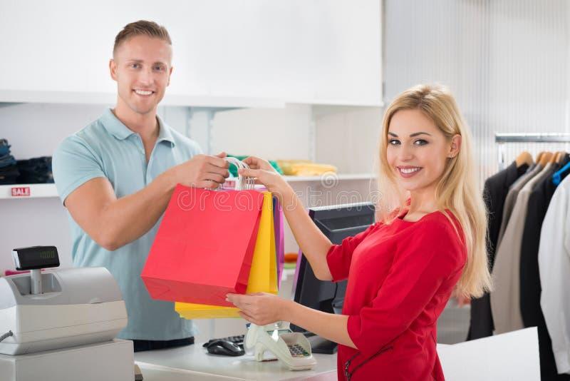 Ευτυχής πελάτης που παίρνει τις τσάντες αγορών από τον πωλητή στο κατάστημα στοκ εικόνα με δικαίωμα ελεύθερης χρήσης
