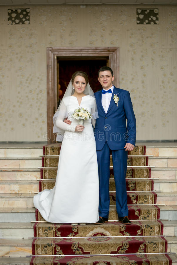Ευτυχής πρόσφατα τοποθέτηση παντρεμένων ζευγαριών στα σκαλοπάτια στην αίθουσα στοκ φωτογραφίες