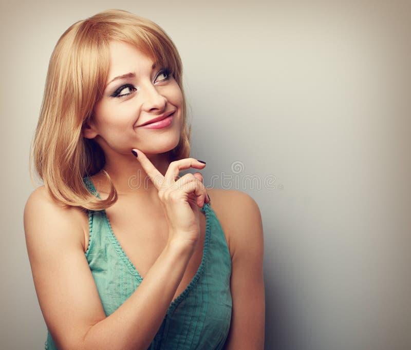 Ευτυχής σκεπτόμενη νέα γυναίκα με το ξανθό σύντομο hairstyle που φαίνεται WI στοκ φωτογραφίες